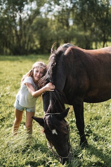 Kleines mädchen im weißen t-shirt und in der jeanshose, die ein pferd umarmen und streicheln