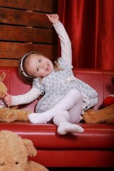 Kleines mädchen im weißen tupfenkleid, das spaß auf der roten couch im weihnachtsstudio hat. weihnachtsbaum, teddybär und geschenkbox auf der vorderseite.