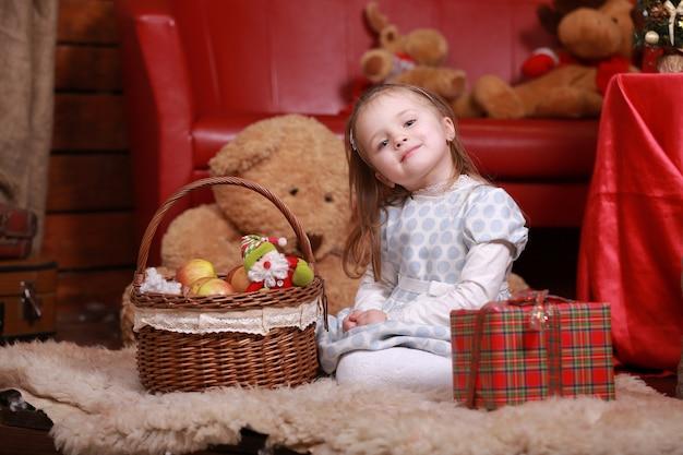 Kleines mädchen im weißen tupfenkleid, das spaß im weihnachtsstudio hat. weihnachtsbaum, teddybär und korb mit geschenken auf der vorderseite.