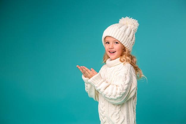 Kleines mädchen im winter strickmütze und pullover