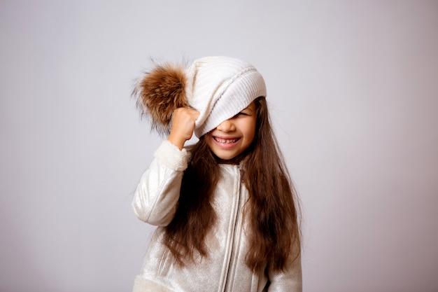 Kleines mädchen im winterhut lächelnd auf weiß