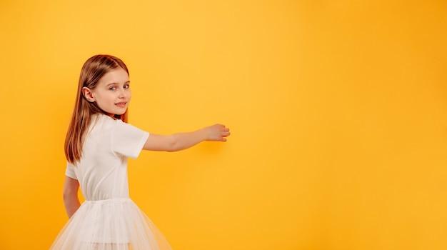 Kleines mädchen imitiert das schreiben auf dem schreibtisch und das betrachten der kamera einzeln auf gelbem hintergrund mit exemplar für ihren text. nettes weibliches kind während der studiofotosession