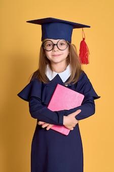Kleines mädchen in akademischer kleidung mit buch