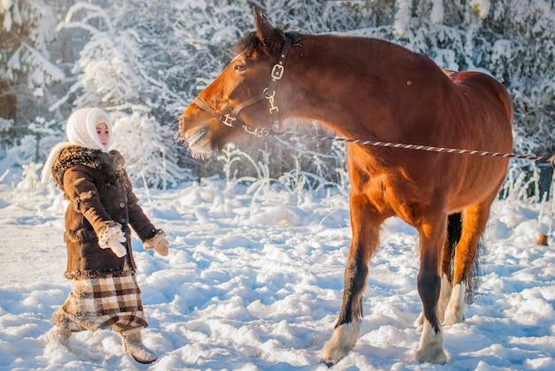 Kleines mädchen in antiken kleidern streckt sich überrascht aus, um ein pferd an einem frostigen sonnigen wintertag zu sehen.