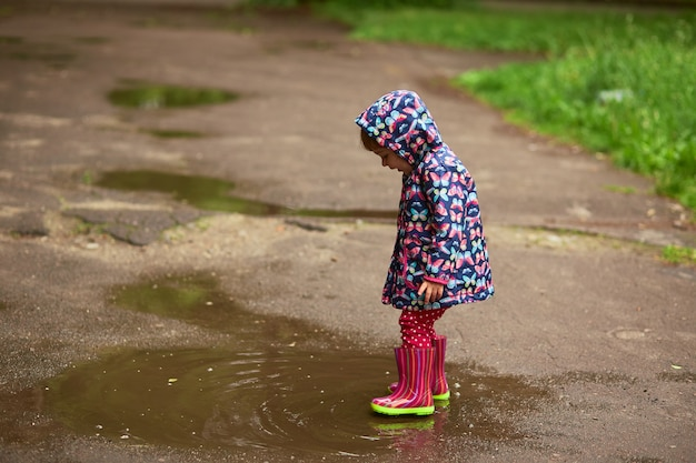 Kleines mädchen in den gumboots hat den spaß, der in die pools nach dem regen geht