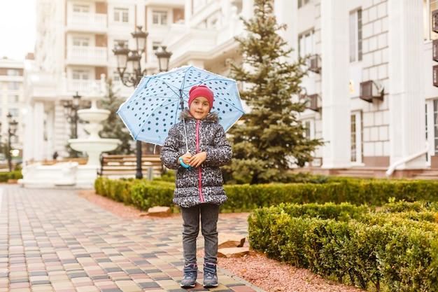 Kleines mädchen in den gummistiefeln, die durch eine pfütze an einem regnerischen tag laufen