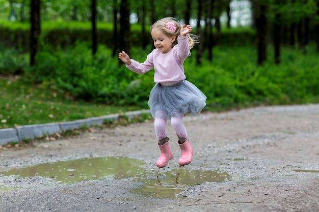 Kleines mädchen in den gummistiefeln und im ballettröckchenkleid, die in pfütze springen.