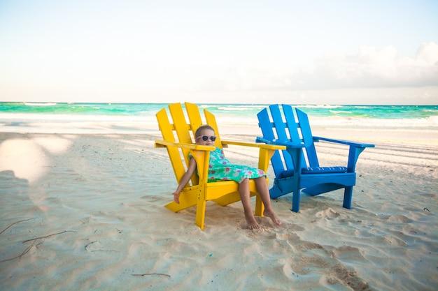 Kleines mädchen in den hölzernen bunten stühlen des strandes auf tropischem tulum setzen, mexiko auf den strand