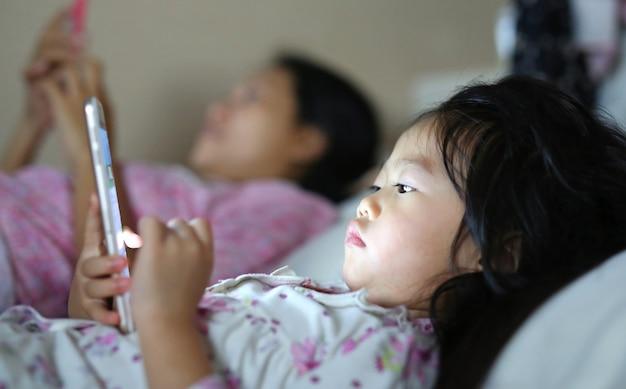 Kleines mädchen in den pyjamas mit der mutter, die den smartphone liegt auf einem bett spielt