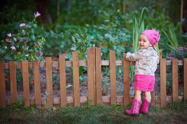 Kleines mädchen in den rosa schuhen nahe dem zaun