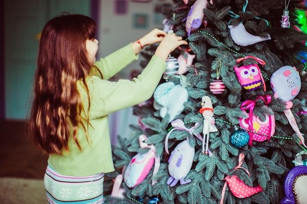 Kleines mädchen in der grünen strickjacke bereitet weihnachtsbaum für die feiertage vor