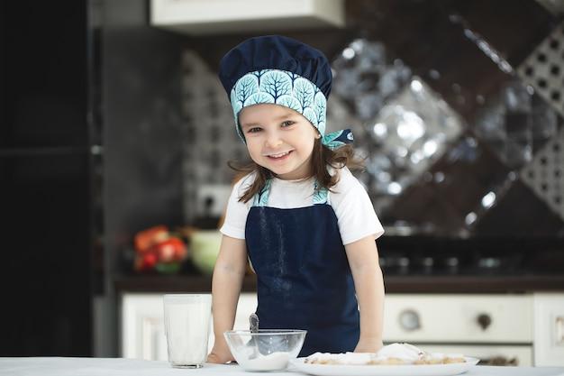 Kleines mädchen in der küche in einer schürze und kochmütze besprüht kekse mit puderzucker