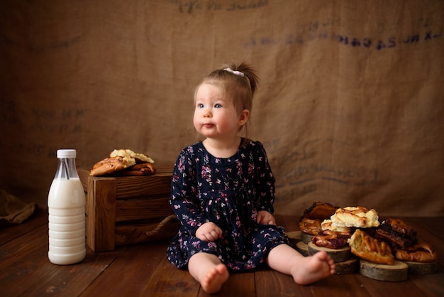 Kleines mädchen in der küche isst süßes gebäck.