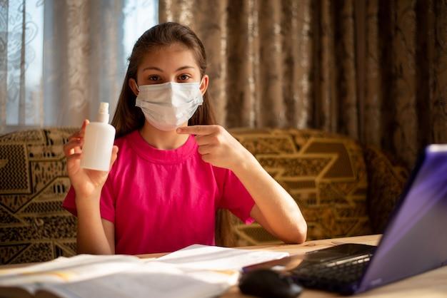 Kleines mädchen in der medizinischen maske, die auf händedesinfektionsmittel zeigt. schulmädchen, das regelmäßig antibakterielles gel verwendet, um sich vor einer gefährlichen covid-19-krankheit zu schützen