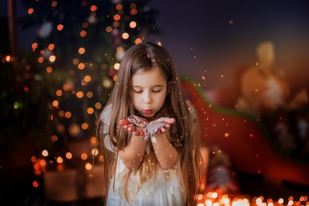 Kleines mädchen in der nähe der weihnachtsbaum lächelnd