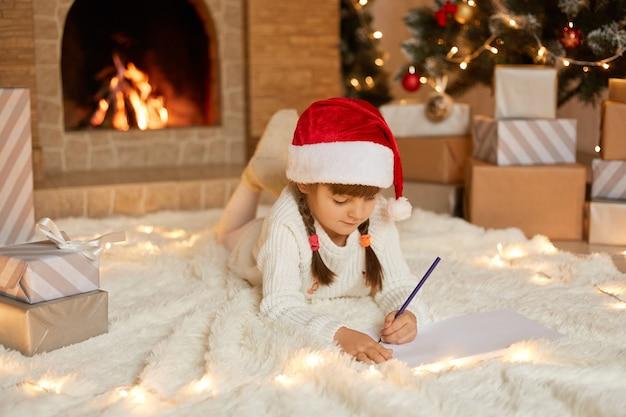 Kleines mädchen in der roten weihnachtsmütze schreibt brief an den weihnachtsmann, entzückendes kind, das auf boden nahe kamin liegt, weißen warmen pullover trägt, auf boden auf weichem teppich liegend.