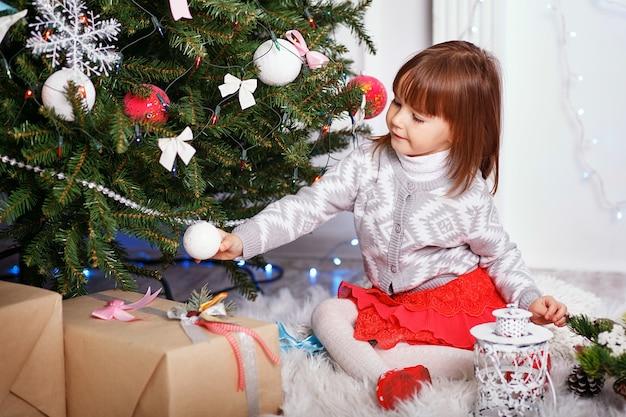 Kleines mädchen in der schönen weihnachtsdekoration. kind, das weihnachtsbaum mit spielzeug und bällen verziert.