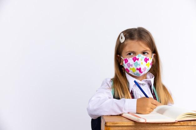 Kleines mädchen in der schule ekelhaft, eine schutzmaske tragend im tisch im unterricht tragend. neue normale schulregeln, gesundheits- und epidemiekonzept.