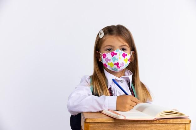 Kleines mädchen in der schule trägt eine schutzmaske, um sich zu schützen, sitzt neben einem tisch mit