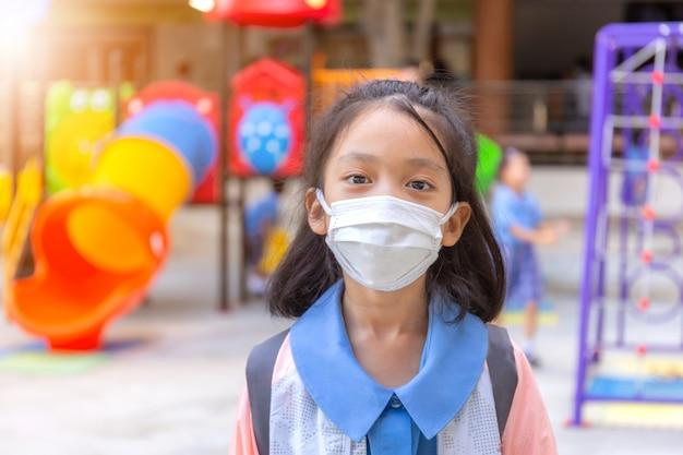 Kleines mädchen in der schuluniform, die eine chirurgische maske mit unscharfem spielplatzhintergrund trägt