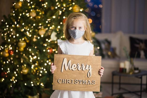 Kleines mädchen in der schutzmaske und im weihnachtsmannhut im dekorierten weihnachtszimmer