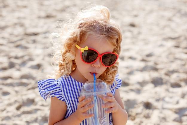 Kleines mädchen in der sonnenbrille, die cocktail am sommerstrand trinkt