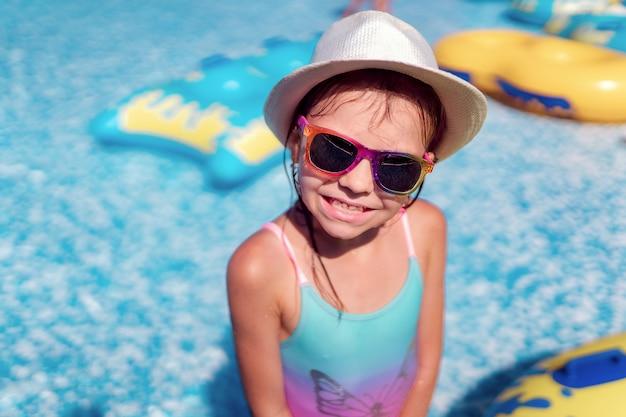 Kleines mädchen in der sonnenbrille und im hut mit einhorn swimmingpool im im freien des luxusresorts auf sommerferien auf tropischer strandinsel