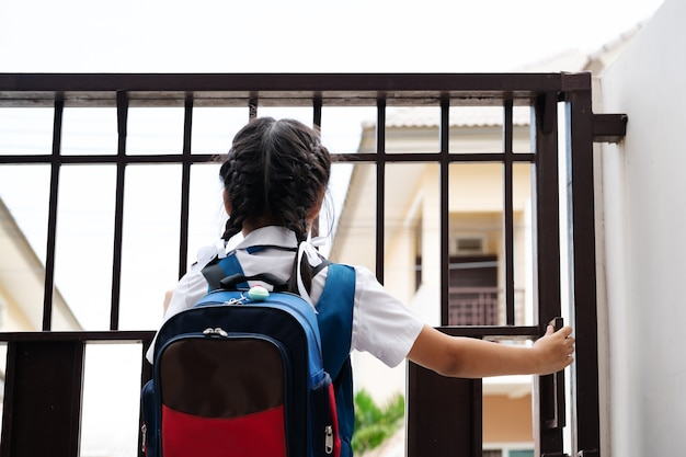 Kleines mädchen in der uniform, welche die tür für das verlassen zur schule morgens mit blauem bac öffnet