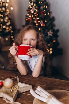 Kleines mädchen in der weihnachtsdekoration mit tee am gemütlichen haus mit bunten neujahrslichtern
