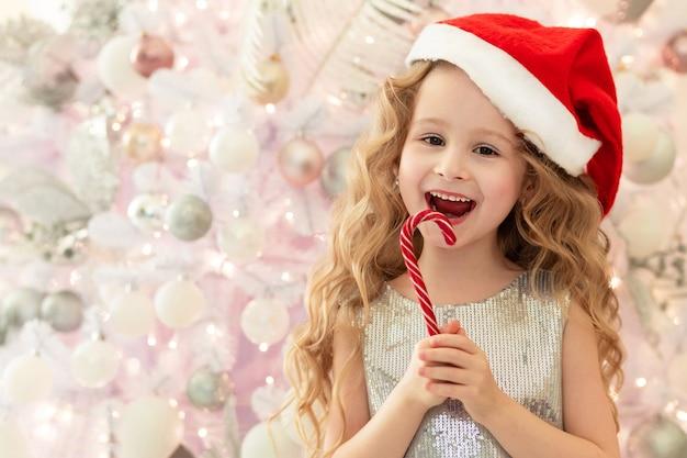 Kleines mädchen in der weihnachtsmütze, die eine lutscher-zuckerstange nahe dem weihnachtsbaum isst.