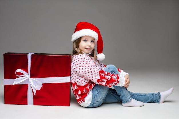 Kleines mädchen in der weihnachtsmütze und im pullover mit wintermuster, das auf rotes weihnachtsgeschenk mit weißer schleife stützt. studioaufnahme auf grauer wand