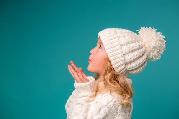 Kleines mädchen in der weißen winterstrickmütze und -strickjacke auf blau