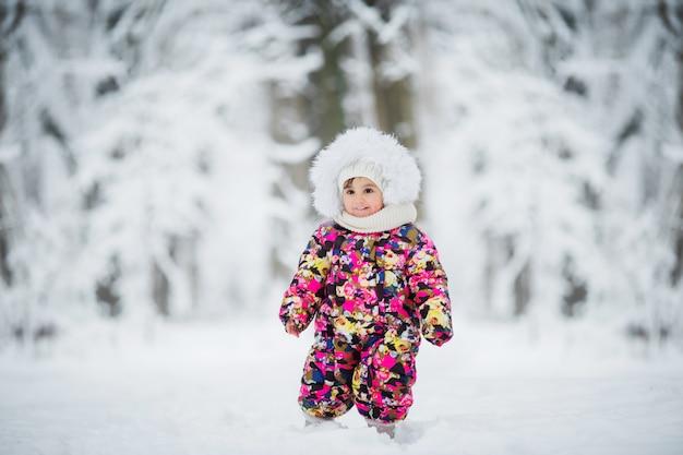 Kleines mädchen in der winterkleidung, die im schnee spielt