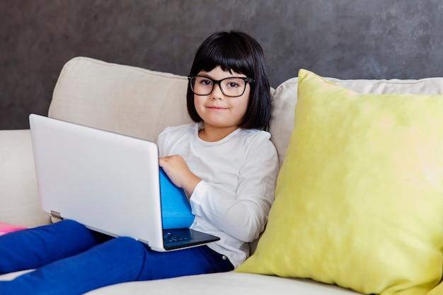 Kleines mädchen in der zufälligen kleidung unter verwendung eines laptops beim auf sofa zu hause sitzen