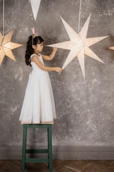 Kleines mädchen in einem abendkleid wirft im raum mit glänzenden dekorativen sternen auf