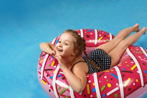 Kleines mädchen in einem badeanzug, der auf einem aufblasbaren kreis des donuts liegt.