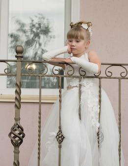 Kleines mädchen in einem ballkleid auf dem balkon