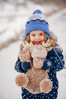 Kleines mädchen in einem blauen hut, der in einem winterwald spielt