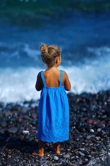 Kleines mädchen in einem blauen kleid, das auf dem paradisos strand in santorini spielt