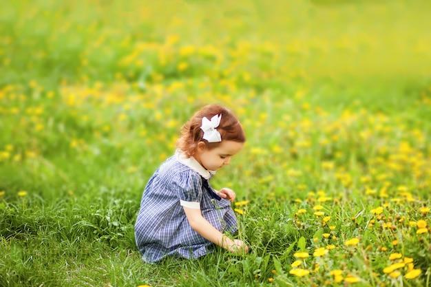 Kleines mädchen in einem blühenden feld mit löwenzahn. retro vintage mode.