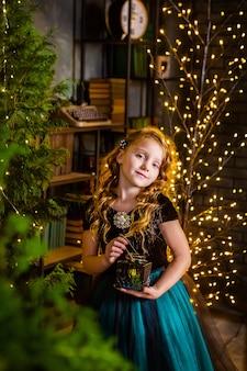 Kleines mädchen in einem festlichen kleid ans langes lockiges haar mit kerze in ihren händen, weihnachtsbaum auf hintergrund. konzept von weihnachten und wundern, neujahrsdekorationen.