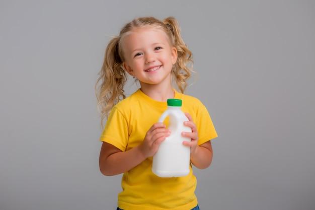 Kleines mädchen in einem gelben t-shirt, das plastikflaschen milch hält
