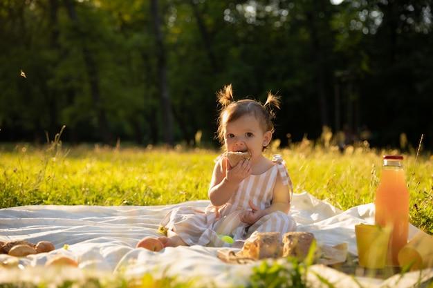 Kleines mädchen in einem gestreiften kleid auf einem picknick in einem stadtpark