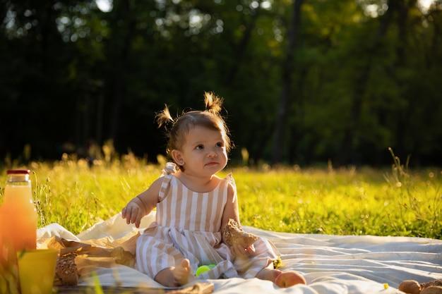 Kleines mädchen in einem gestreiften kleid auf einem picknick in einem stadtpark.