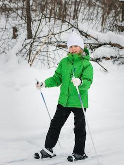 Kleines mädchen in einem hellgrünen anzug lernt, im wald ski zu fahren