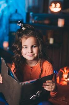 Kleines mädchen in einem hexenkostüm mit zauberbuch