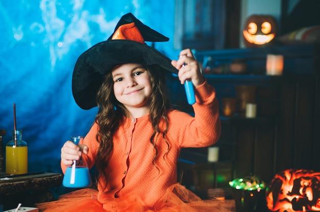 Kleines mädchen in einem kostüm der hexe, die trank macht