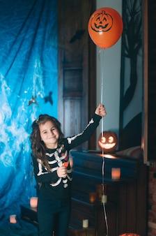 Kleines mädchen in einem kostüm des skeletts, das orange ballon hält