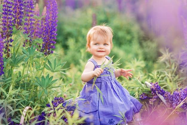 Kleines mädchen in einem lila sommerkleid, das in der natur sitzt. kind in blumen