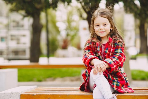 Kleines mädchen in einem park, der auf einer bank sitzt